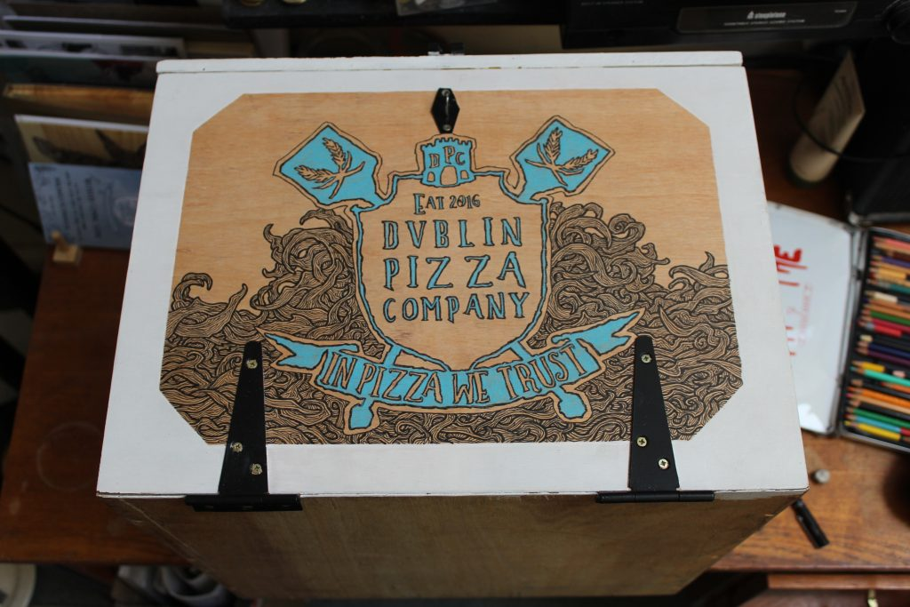Illustration on wooden delivery box of Dublin Pizza Company in ireland with colouring pencil, pen and ink by Dublin based illustrator John Rooney